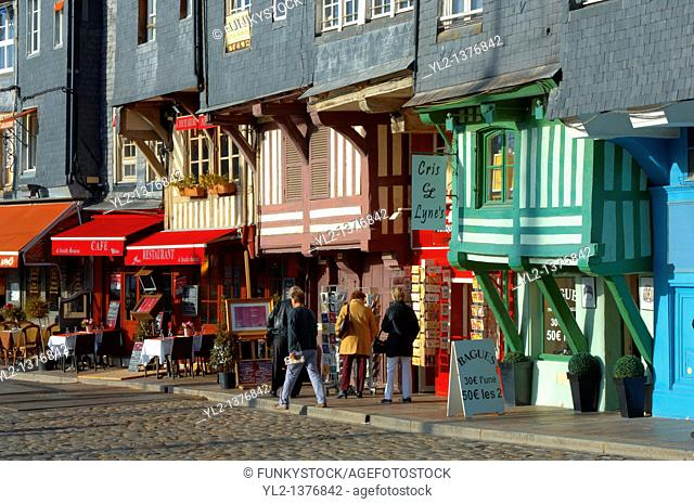 Harbour sided shops with an older couple looking in the window with arms around each other  Honfleur, Normandy, France