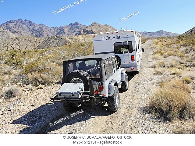 Recreational vehicle towing Jeep going up old dirt mine road, Providence Mountains, Mojave Desert, California, USA