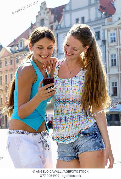Prague. Czech Republic. Two young women in Old Town Square of Prague watching photos on a smart phone