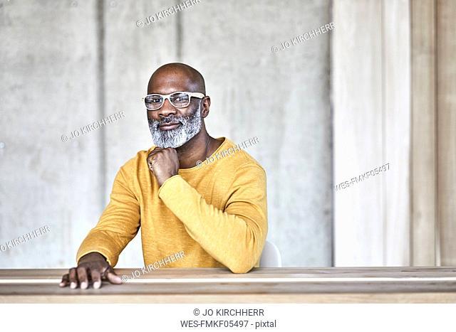 Portrait of confident mature businessman sitting at desk in office