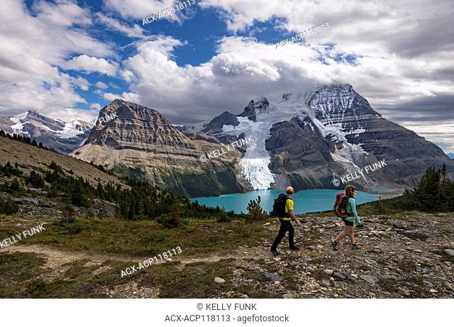 A young man and woman checks the view while on the Mumm Basis trail with Mt. Robson and Rearguard mountain in the background, Mt
