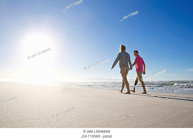 Low Angle Shot Of Man With Artificial Leg Walking Along Beach Holding Hands With Female Partner On Summer Vacation