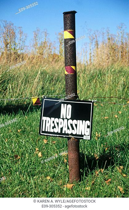 'No trespassing' sign in field near weeds, Indiana, USA