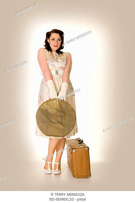 Innocent looking young woman with suitcases, retro style