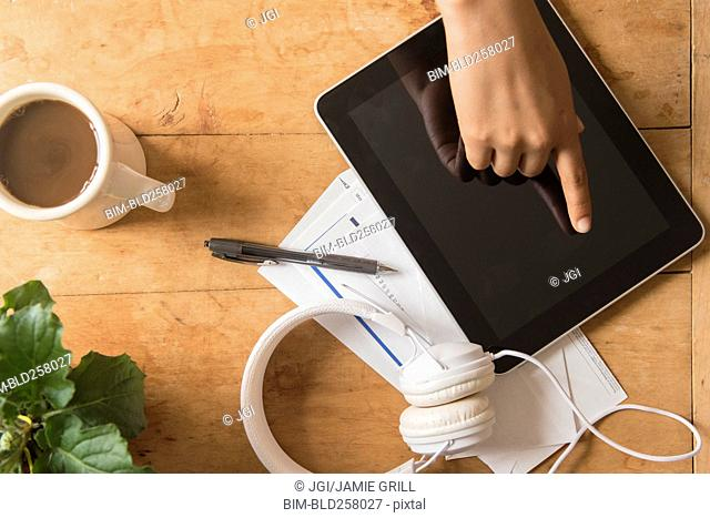 Finger of African American woman touching digital tablet