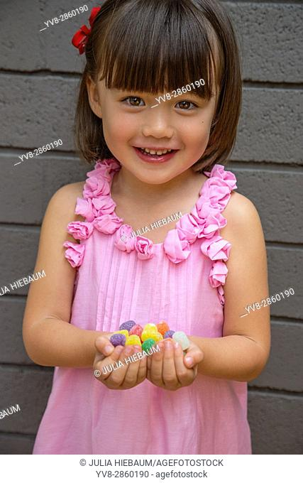 Four year old holding colorful candies