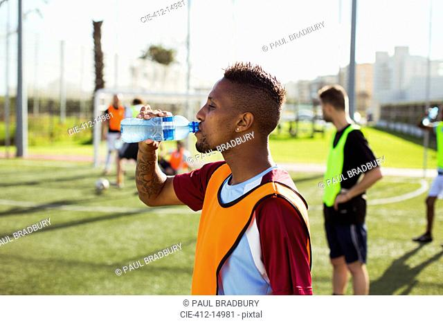 Soccer player drinking water on field