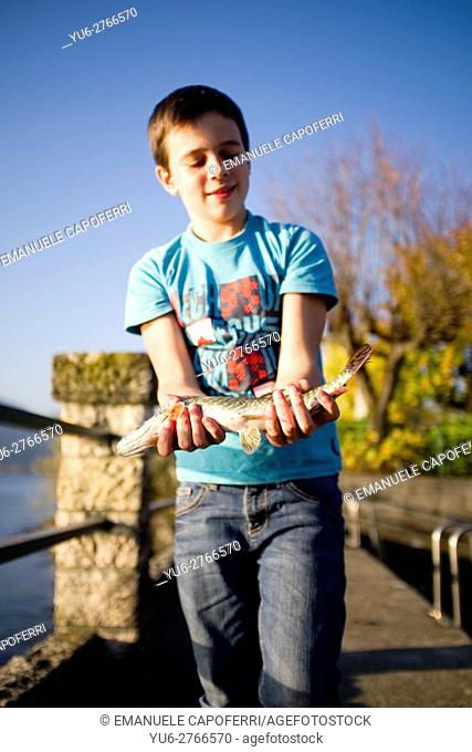 12 year old boy with freshly caught fish, Pike