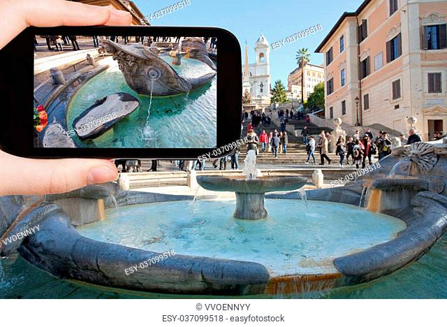 travel concept - tourist taking photo of Fountain of the Old Boat Spanish square with Spanish Steps on background, Rome on mobile gadget, Italy