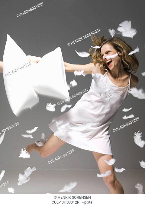 Woman having pillow fight