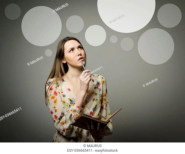 Thoughtful girl holding pen and notebook. Girl having an idea with gray bubbles over her head