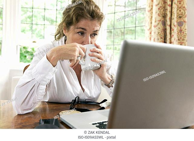 Worried mature woman working on laptop whilst drinking coffee in living room