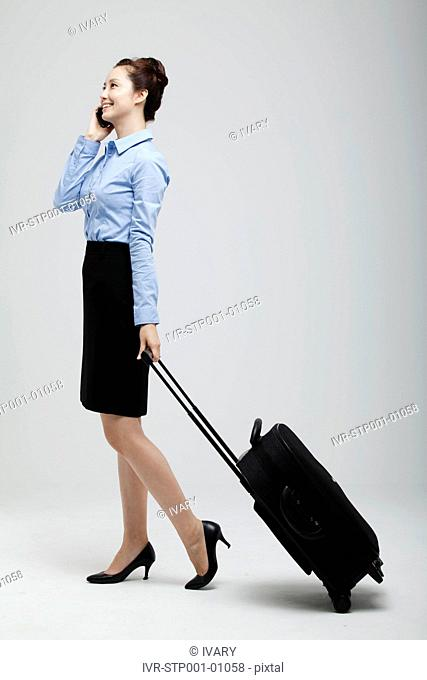 Asian Businesswoman Standing With Luggage Using Cell Phone