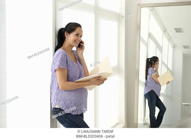 Pregnant Hispanic woman talking on cell phone