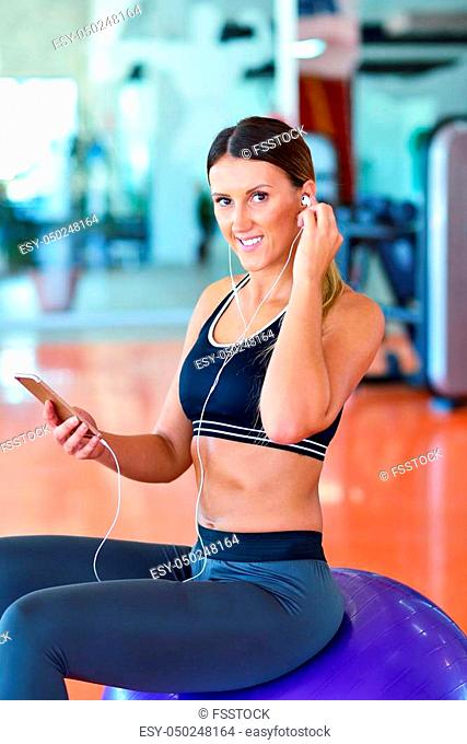 Sportswoman using a mobile phone in the gym