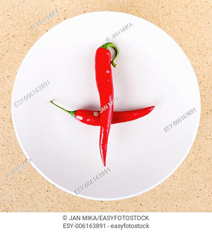 Two fresh raw red hot chili peppers on plate arranged in cross or plus shape
