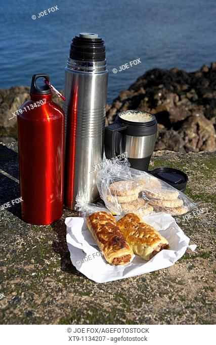 lunch including sausage rolls biscuits flasks and coffee on rocks on the county antrim coast northern ireland