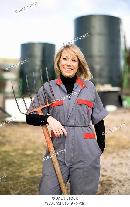 Woman working on fram, holding hay fork