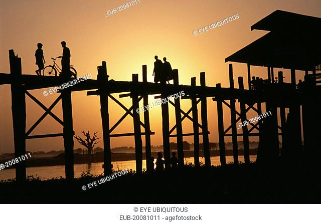 U Bein Bridge near Mandalay at sunset with silhouetted figures of monks, child and cyclist crossing