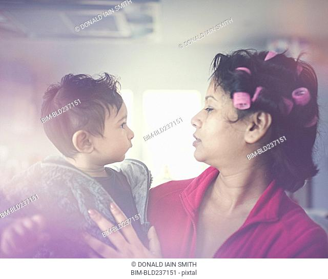 Indian mother wearing curlers holding son