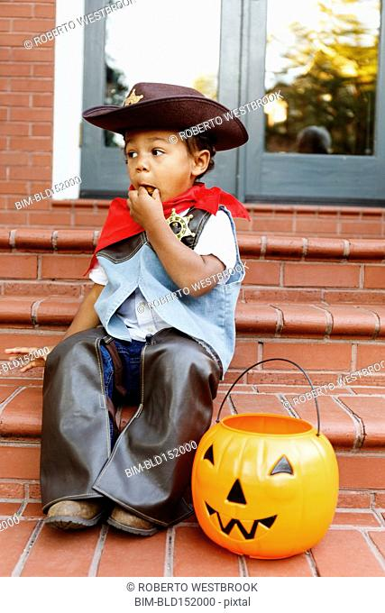Mixed race boy dressed as cowboy eating Halloween candy