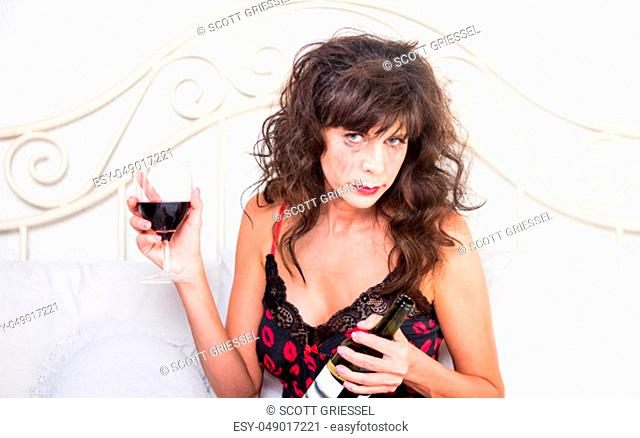 Upset mature woman crying and drinking wine in her bedroom