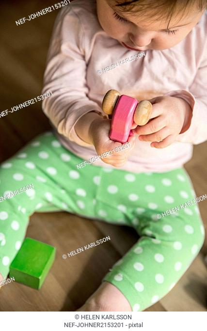 Baby girl playing with wooden car