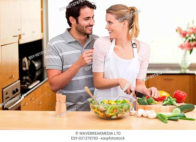 Young couple slicing vegetables