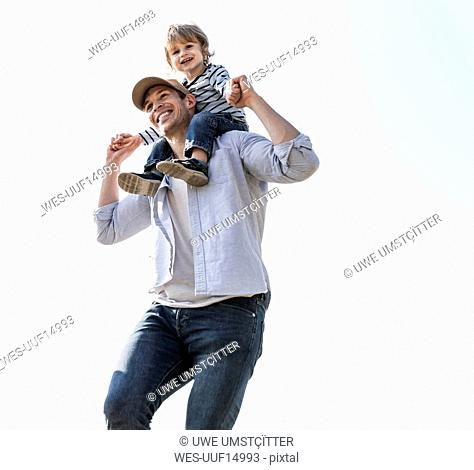 Happy father carrying son on his shoulders