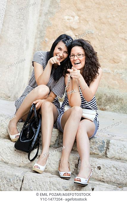 Two attractive young women are laughing on a staircase pointing with a finger to the camera