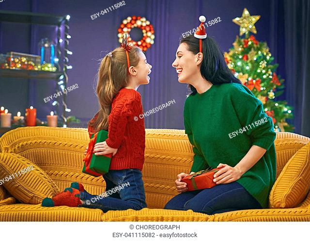 Merry Christmas and Happy Holidays! Cheerful mom and her cute daughter girl exchanging gifts. Parent and little child having fun near tree indoors