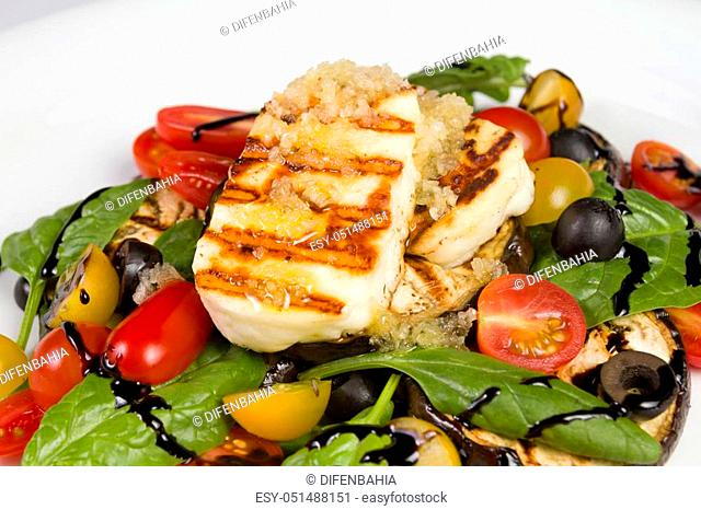Grilled Halloumi Cheese poured with garlic olive oil salad witch grilled eggplant, cherry tomatoes, black olives and spinach. healthy food. Close up