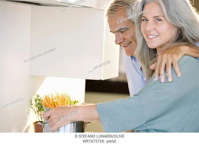 Mature couple cooking spaghetti