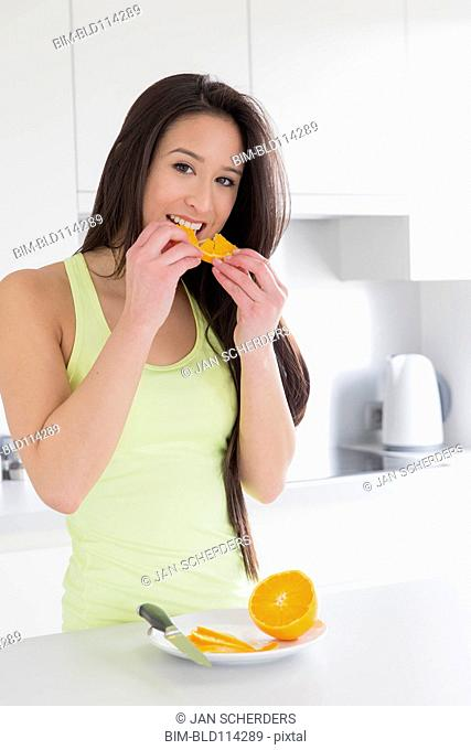 Mixed race woman eating fruit in kitchen