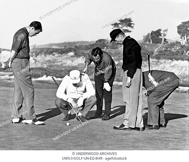California: c. 1952. Five golfers gather around to ponder a ball perched on the very lip of the cup