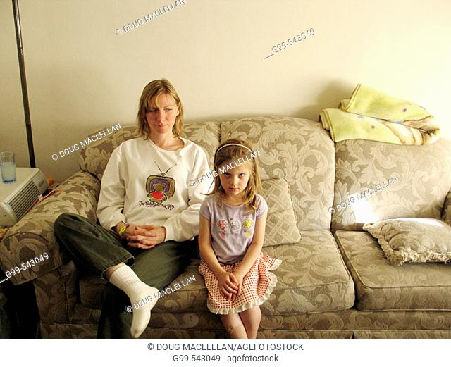 A quizzical looking four year girl stares while her mother watches in Windsor, Ontario, Canada