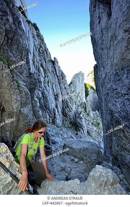 Woman ascending through canyon Kaisersaele to Kampenwand, Chiemgau Alps, Chiemgau, Upper Bavaria, Bavaria, Germany