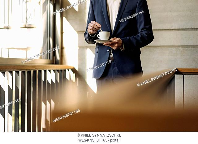 Businessman with cup of coffee in staircase