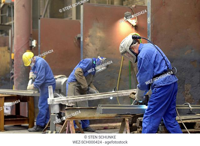 Workers deburring cast iron parts in a foundry