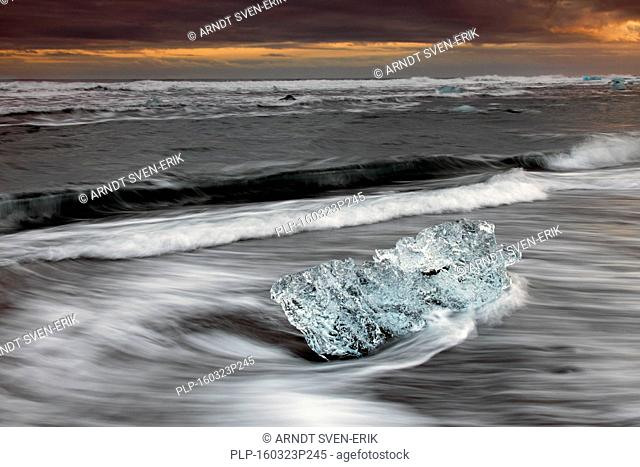 Melting block of ice washed on beach along the Atlantic Ocean coastline at Breidamerkursandur black sands in winter, Sudursveit, Iceland