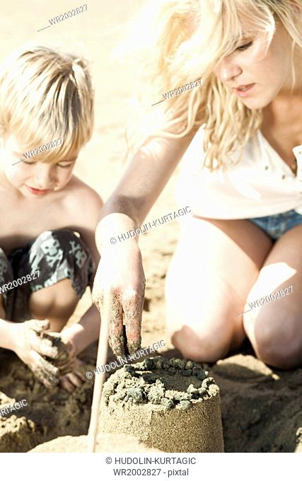 Mother and son on beach making sandcastle