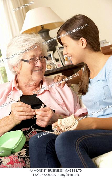 Grandmother Showing Granddaughter How To Crochet At Home