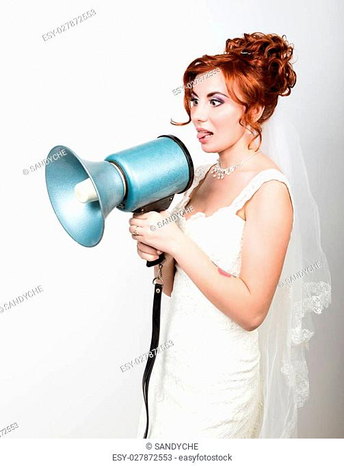 beautiful bride in a wedding dress with a wedding makeup and hairstyle, she yells into a bullhorn. Public Relations