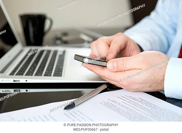 Businessman sitting at desk text messaging, partial view