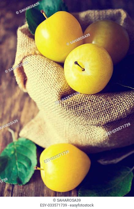 Ripe yellow plums in a bag on a vintage table. Close-up. Bio healthy food. Organic fruits. Tinted image. Selective focus