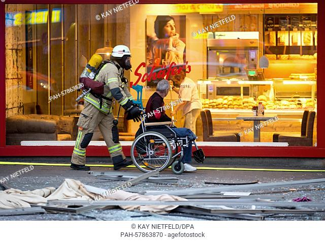 A fire fighter (L) removes a resident from a building where a fire occurred in Berlin,Germany, 28 April 2015. One person was killed