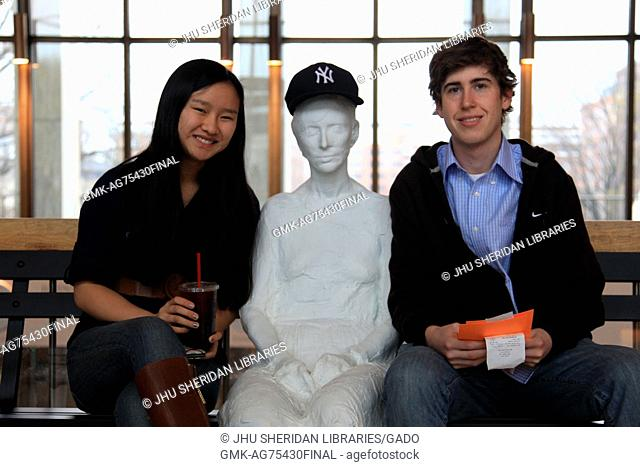 """Members of the Johns Hopkins University and Baltimore communities pose with """"""""Woman With Sunglasses"""""""", a painted bronze sculpture by artist George Segal"""