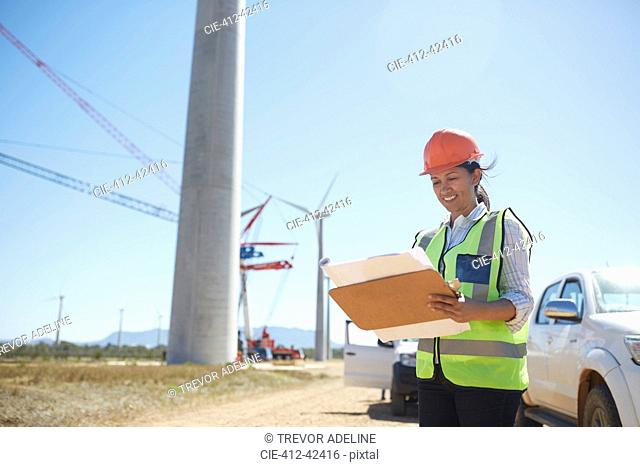 Smiling female engineer with blueprint at sunny wind turbine power plant