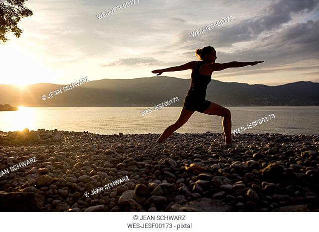 Young woman doing yoga at the stony beach at sunset, Warrior pose