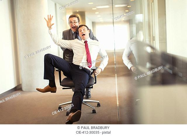 Playful businessman pushing colleague down corridor in office chair